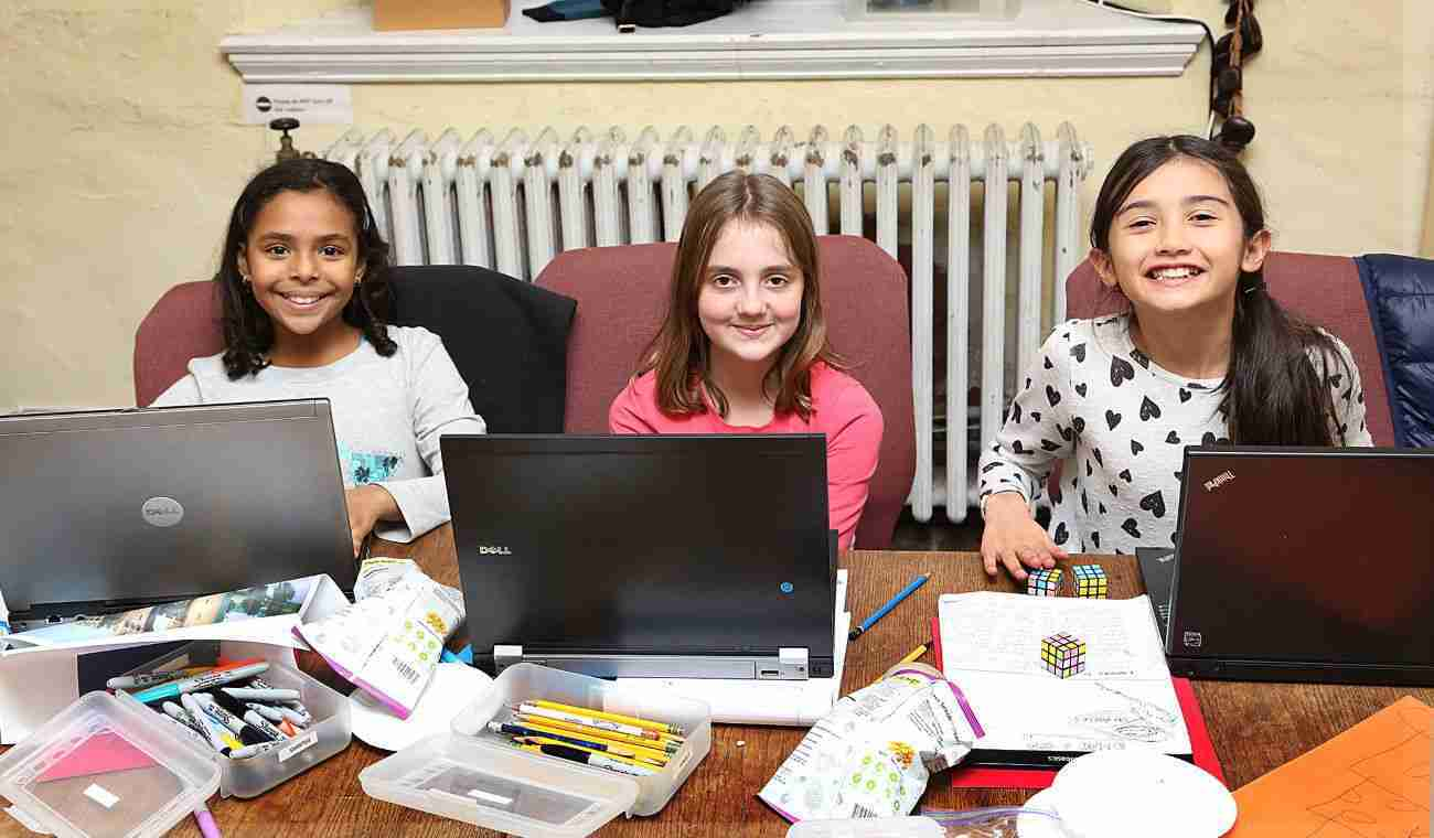 Three girls sitting in front of laptops look up smiling