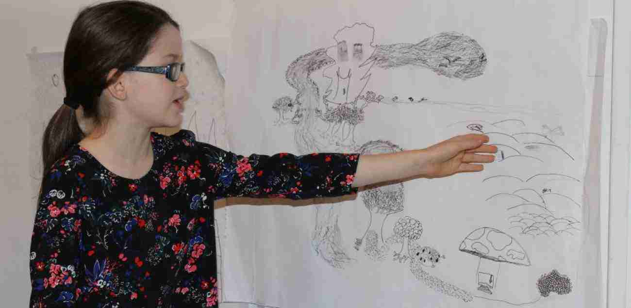 Girl points to section of comic drawing